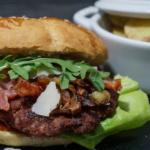 Burger mit karamellisierten Zwiebeln, Bacon, Barbecue-Sauce und etwas Grün