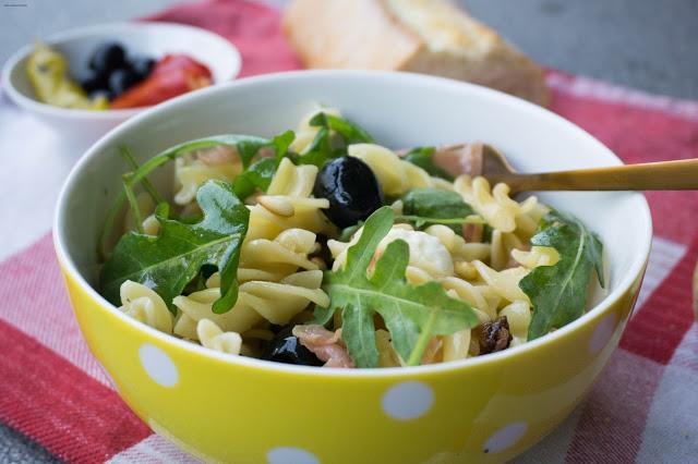 Italienischer Nudelsalat mit Rucola, Oliven, Mozarella und Serano Schinken.